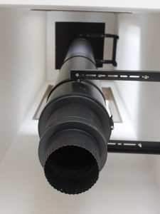 屋根から吹き抜けを通って1階までまっすぐな煙突を設置中