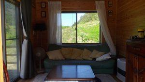 小屋はソファーベッドがあり後ろの窓からはバラと菊園が見える