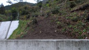 重力擁壁の横から運搬機で運び上から庭の横の土留めの間に表土を入れた