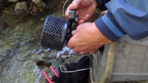 取水カバーをモルタルで固めた重石に通したパイプの先端につける固定する